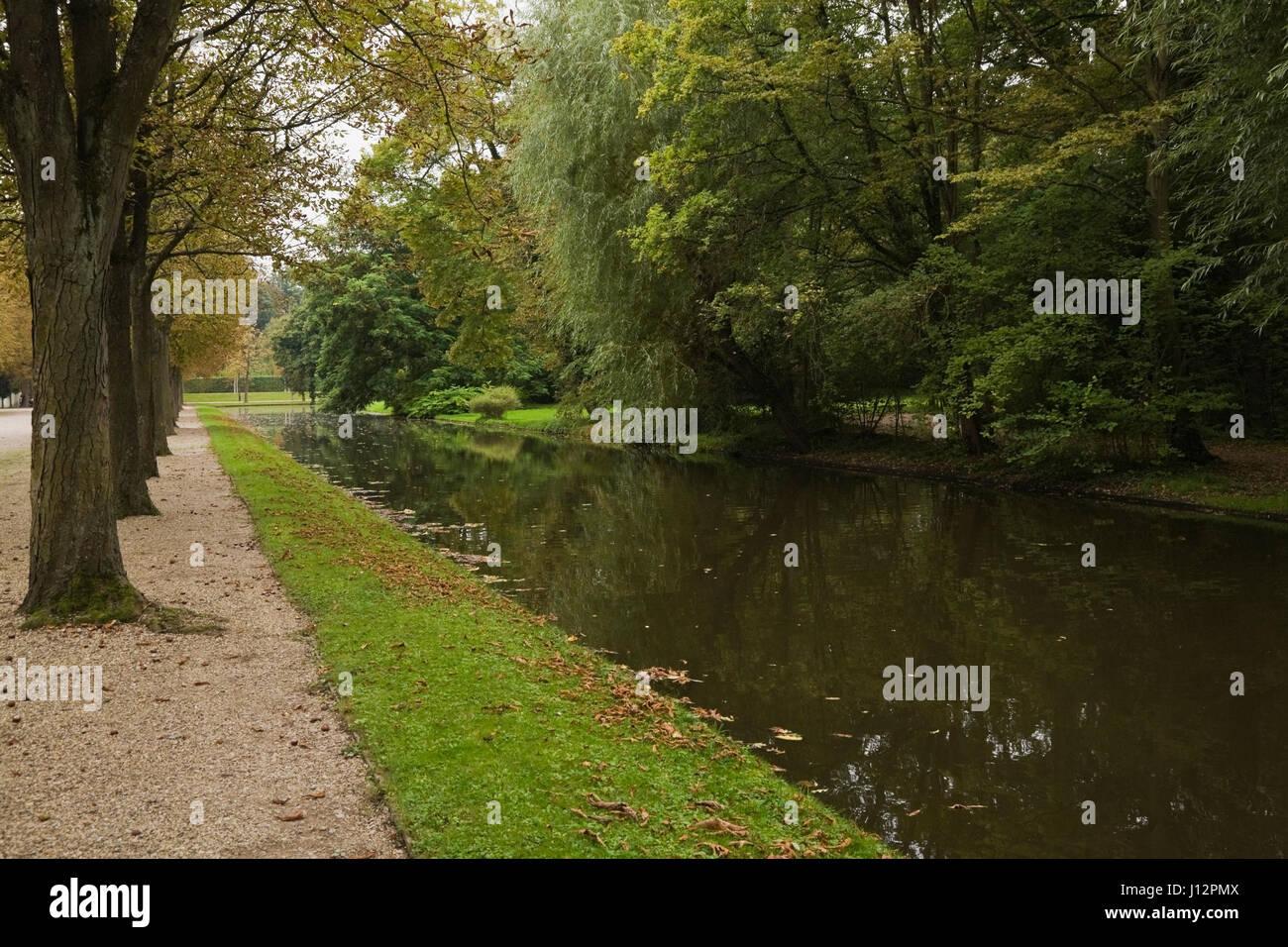 Water canal with row of deciduous trees in the Schwetzingen palace garden in late summer, Schwetzingen, Germany - Stock Image