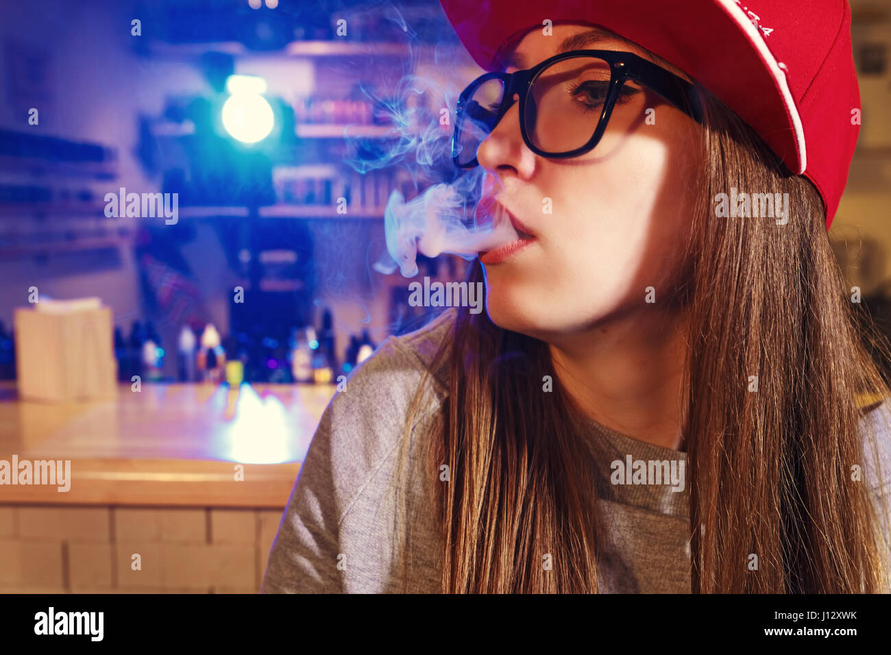 Young pretty woman in red cap smoke an electronic cigarette at the vape shop. Closeup. - Stock Image
