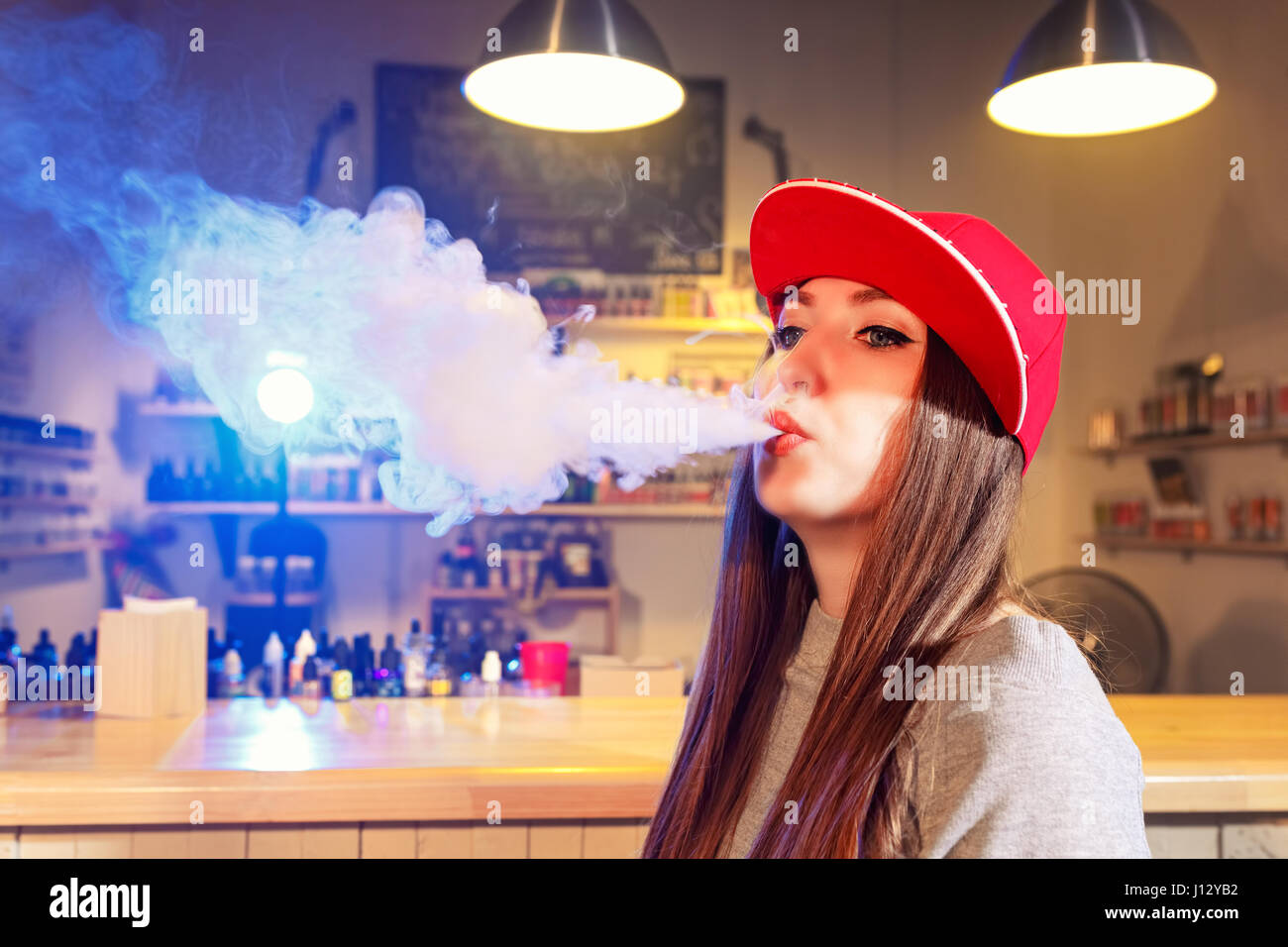 Young pretty woman in red cap smoke an electronic cigarette at the vape shop - Stock Image