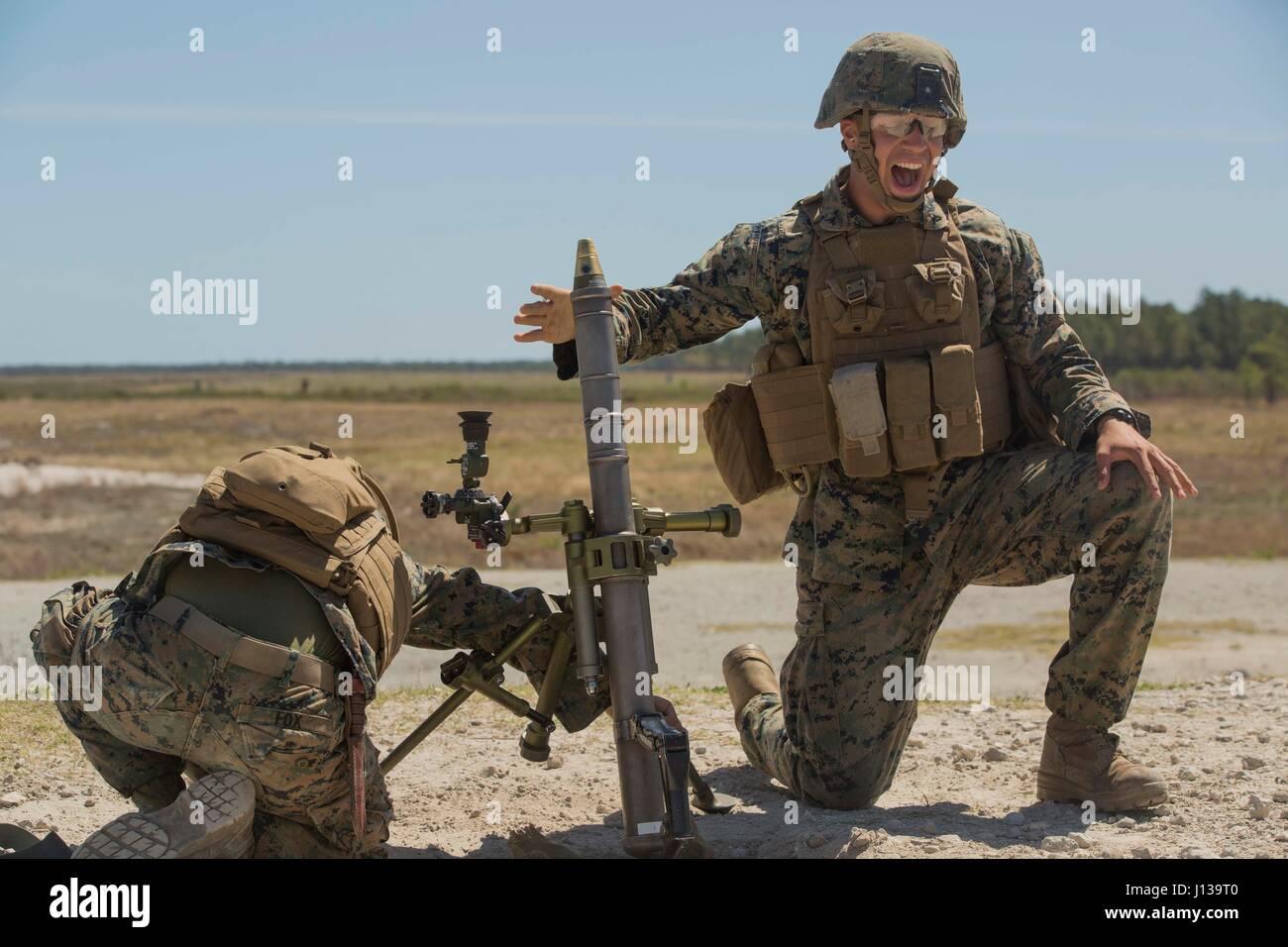 A Marine drops a 60mm mortar into an M224 mortar system