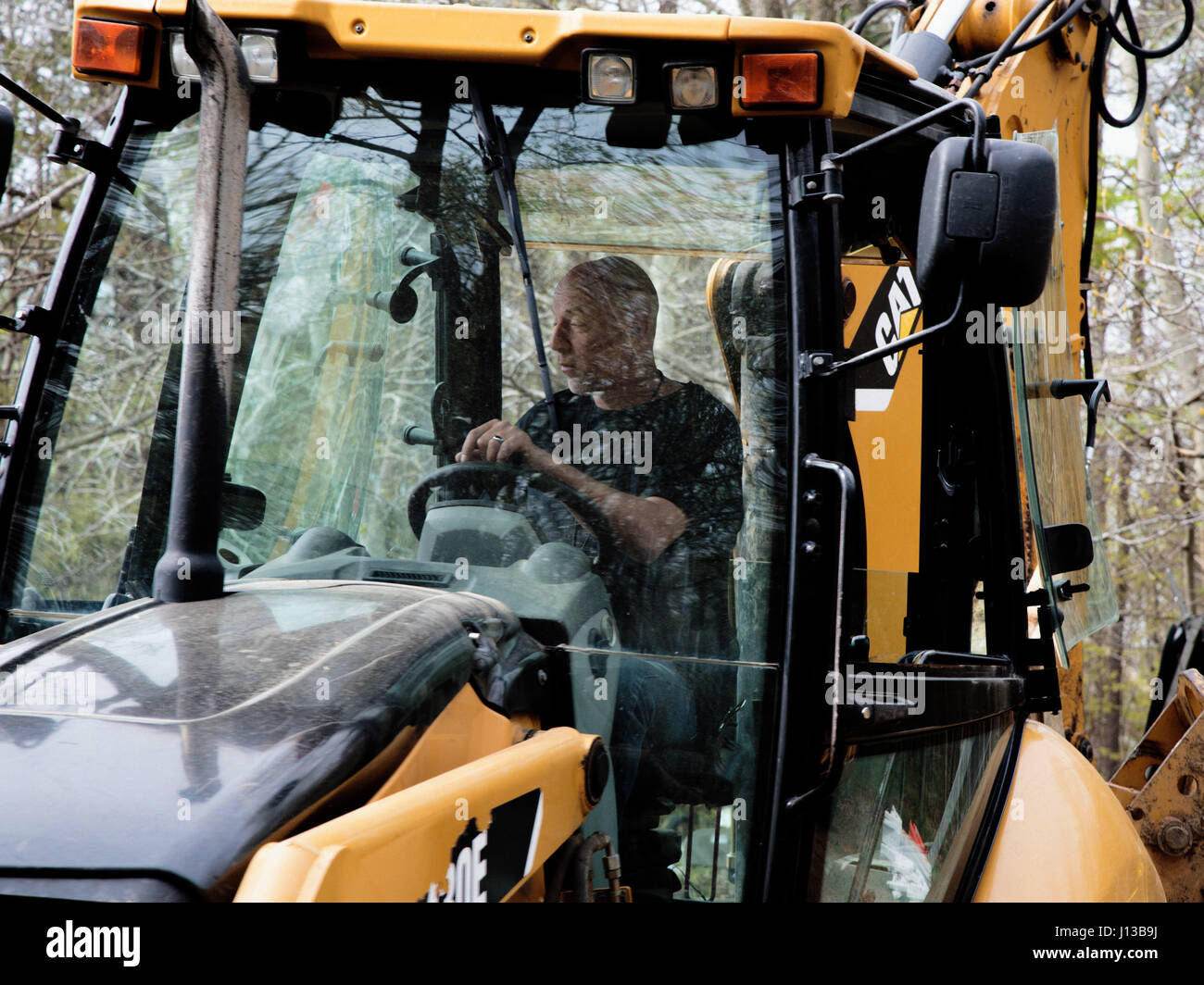 Carlos Procter, 11th Civil Engineer Squadron heavy equipment operator, drives a tractor-loader-backhoe in Clinton, - Stock Image