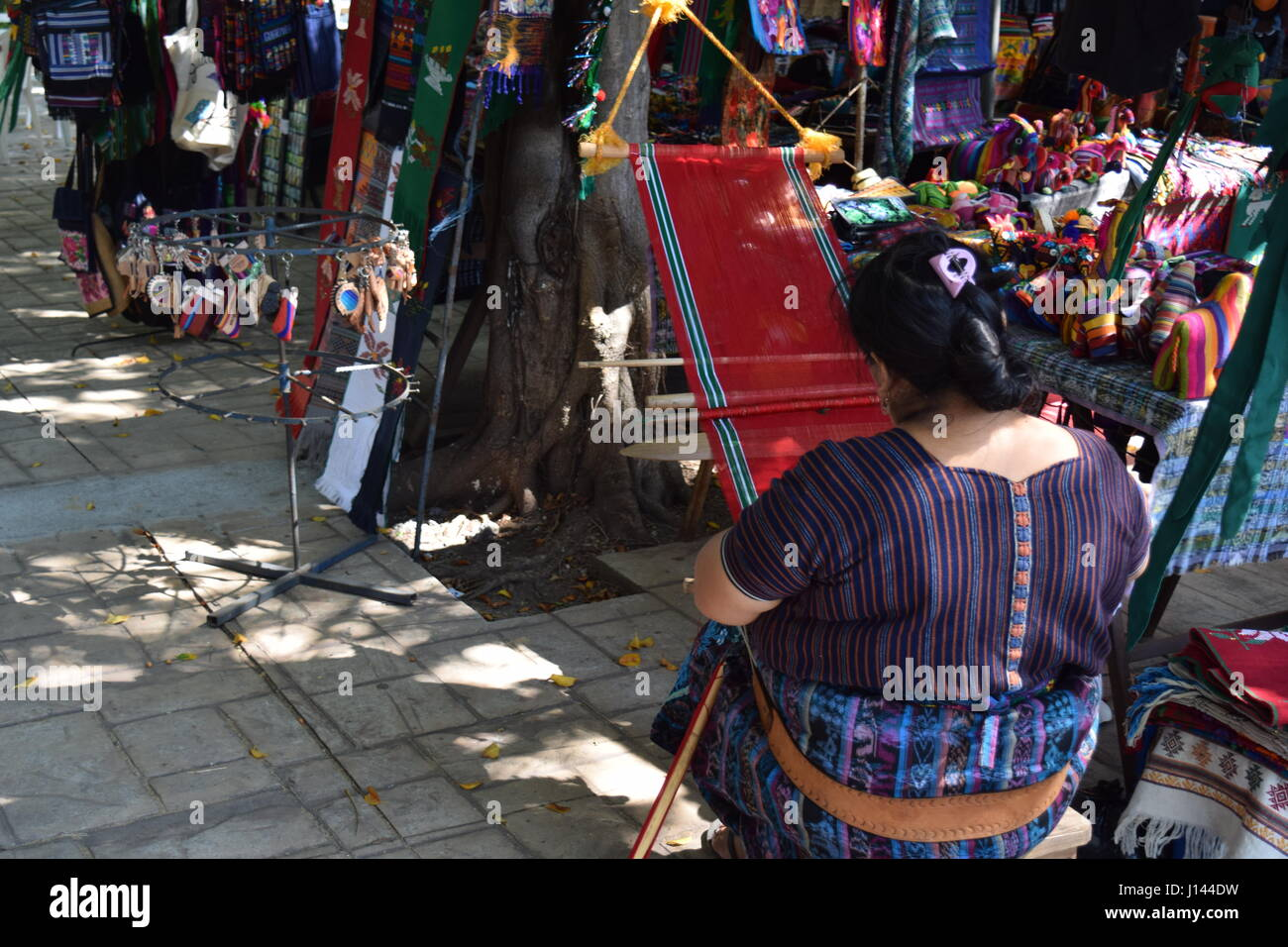 Indigenous woman working textiles on the loom, in Puerto San Jose,  Guatemala - Stock Image