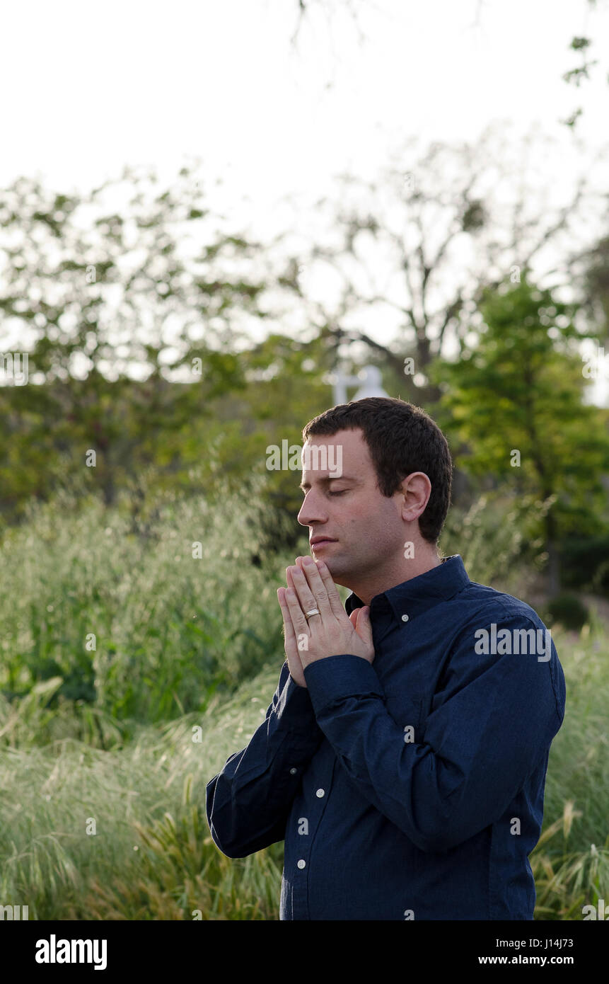 Man praying with his hands together outside wearing a button down shirt. - Stock Image