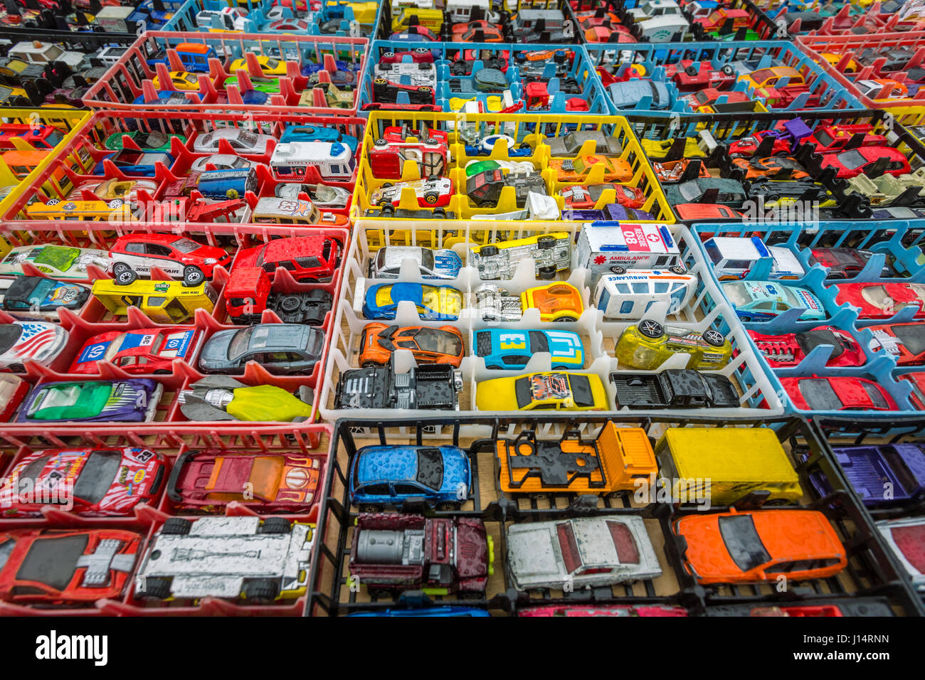 Boxes of toy cars autos on sales in a market - Stock Image
