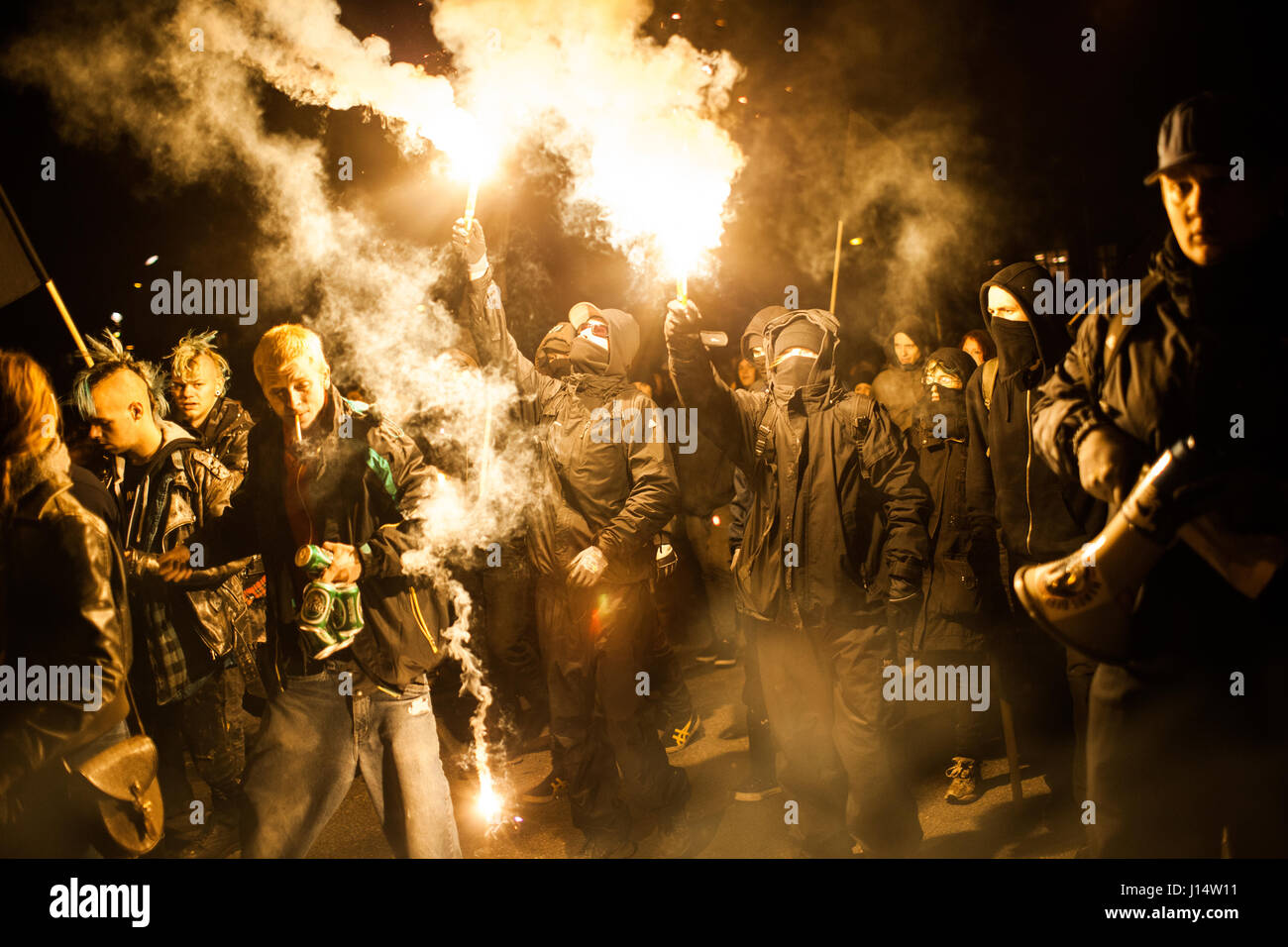 Left wing protesters made the demonstration more colorful firing up flares while marching the streets of the Copenhagen - Stock Image