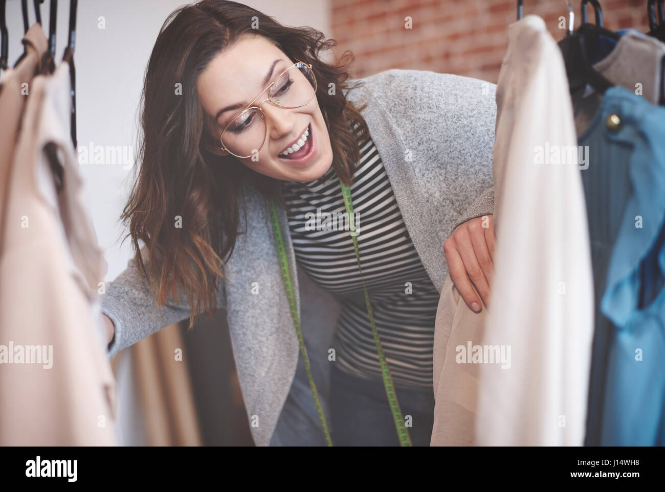 Young seamstress looking through on hangers - Stock Image