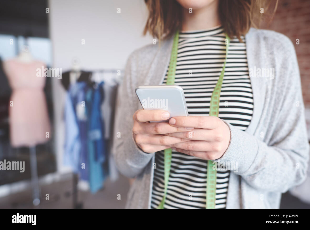 Small business owner text messaging - Stock Image