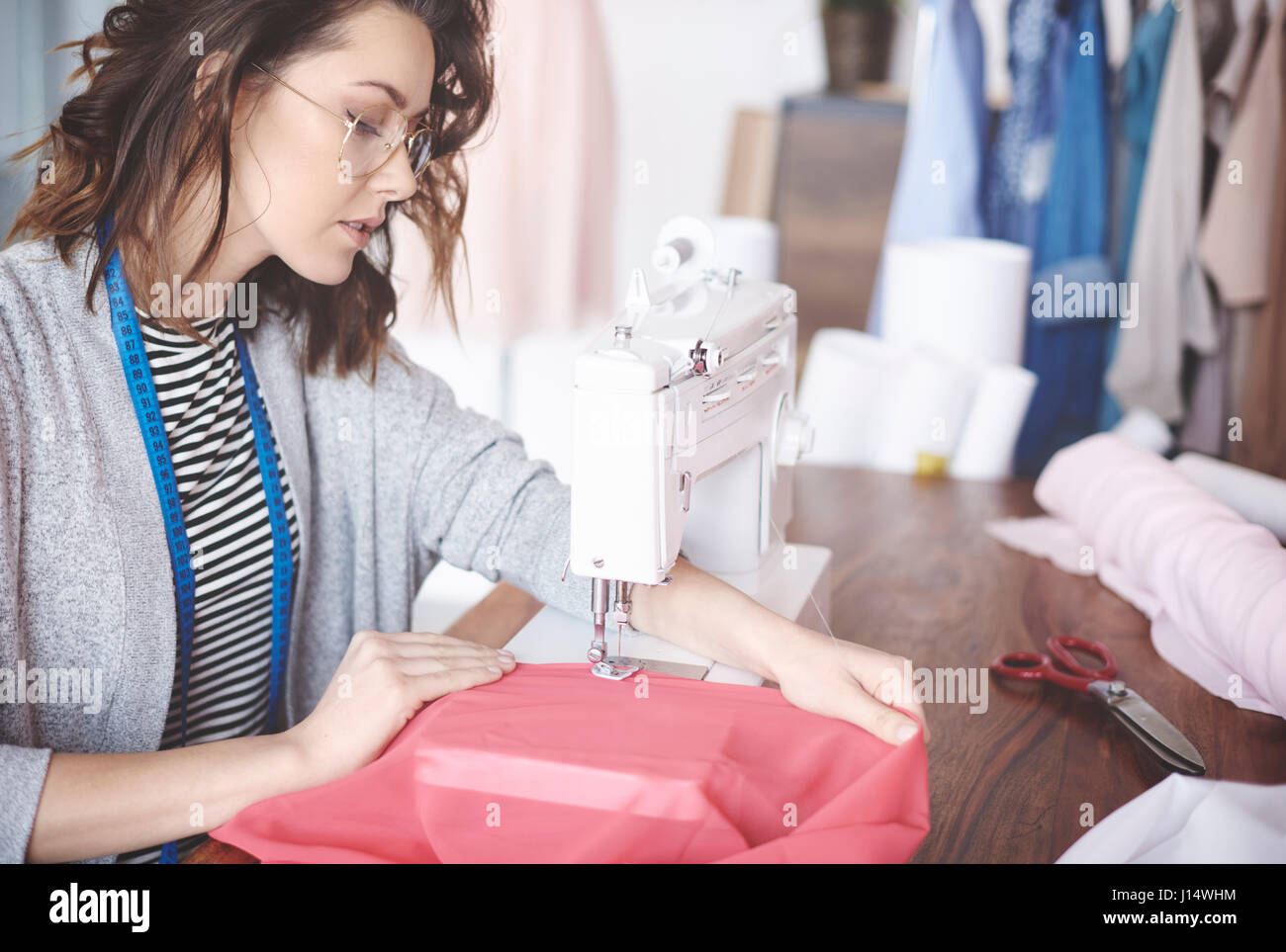 Skilled young tailor sewing on machine - Stock Image