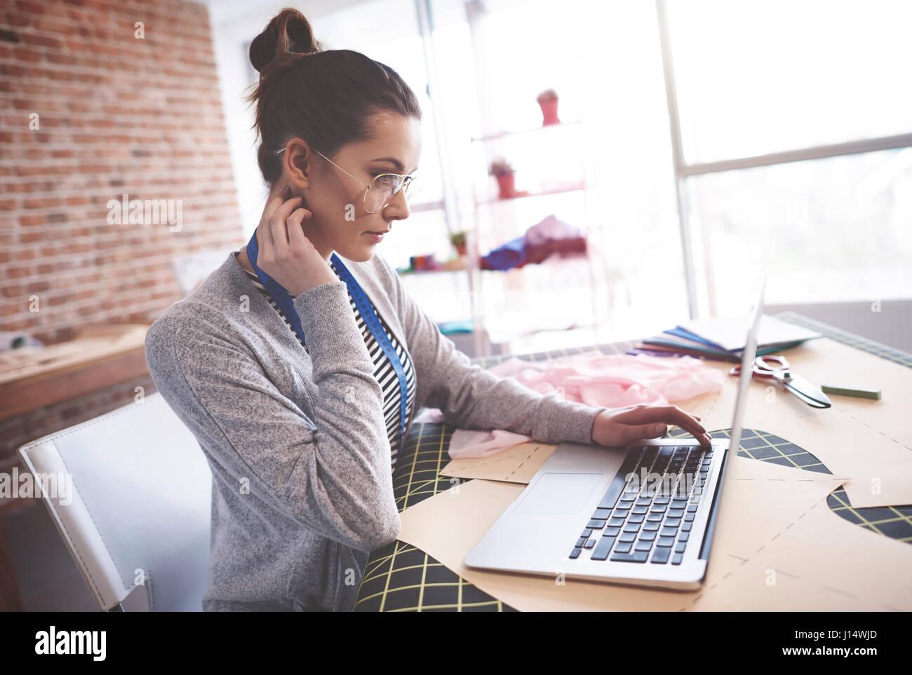 Clothing designer working on laptop - Stock Image
