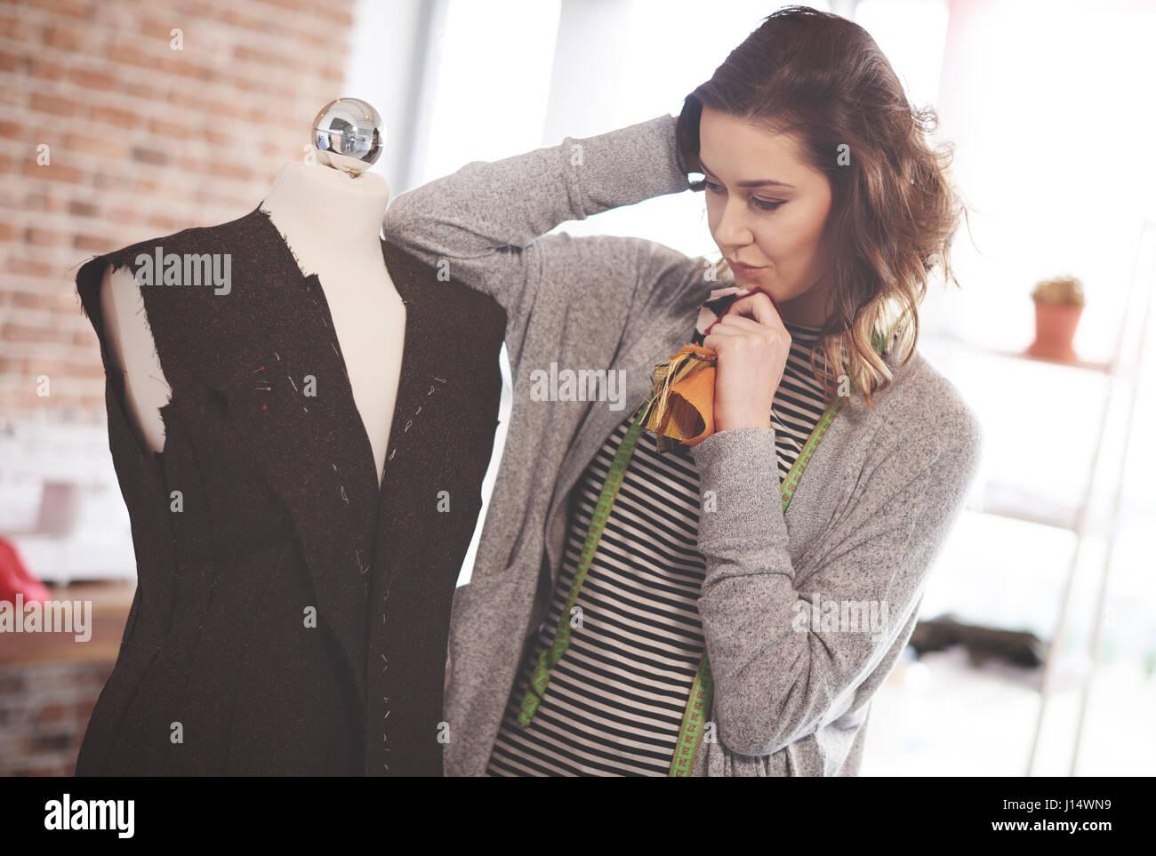 Female fashion designer thinking about changes - Stock Image