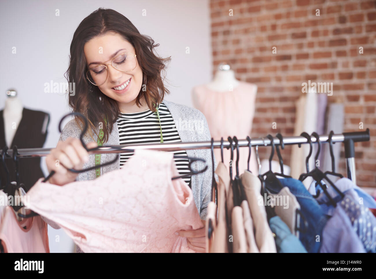 Fashion designer searching outfits on clothing racks - Stock Image