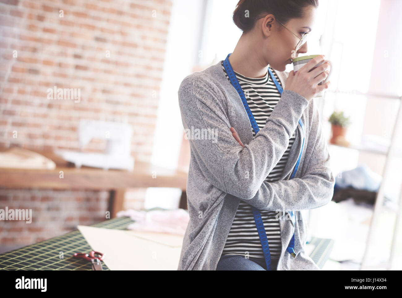 Tailor having coffee break at her office interior - Stock Image