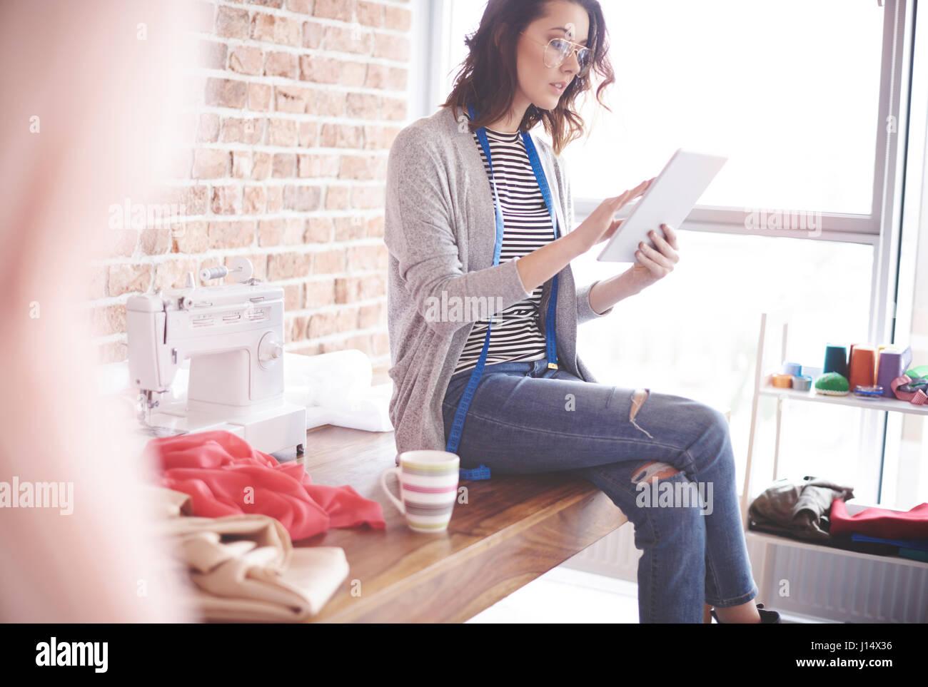 Fashion designer with digital tablet at her studio - Stock Image