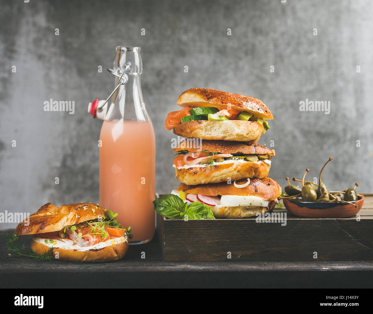 Bagels with salmon, eggs, vegetables, capers, cream-cheese and grapefruit lemonade - Stock Image