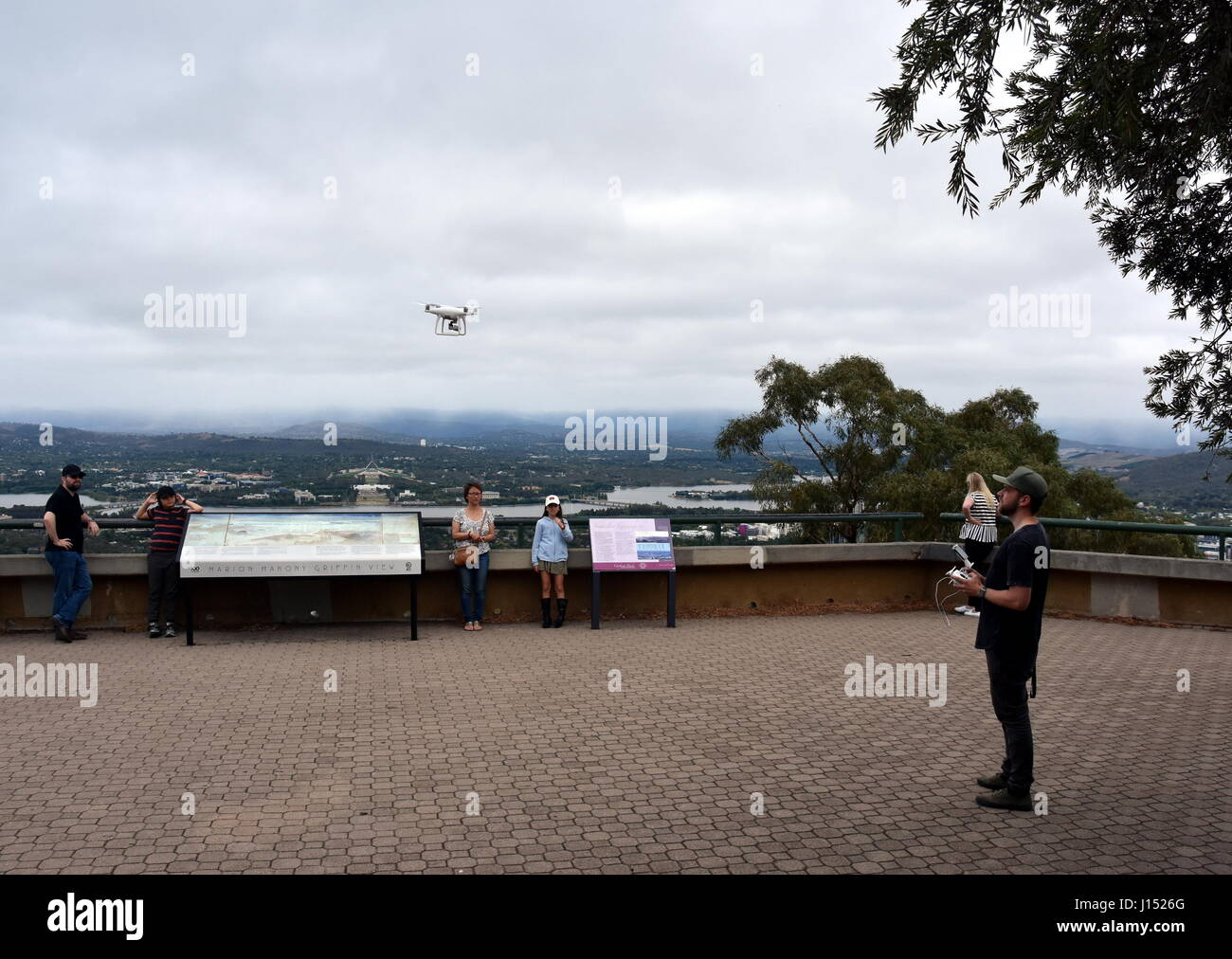 Canberra, Australia - March 19, 2017. A guy playing with a white drone at Mount Ainslie lookout. - Stock Image