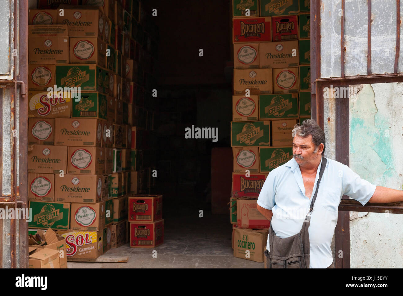 A man standing in front of building used for storing cases of beer in Havana, Cuba. - Stock Image