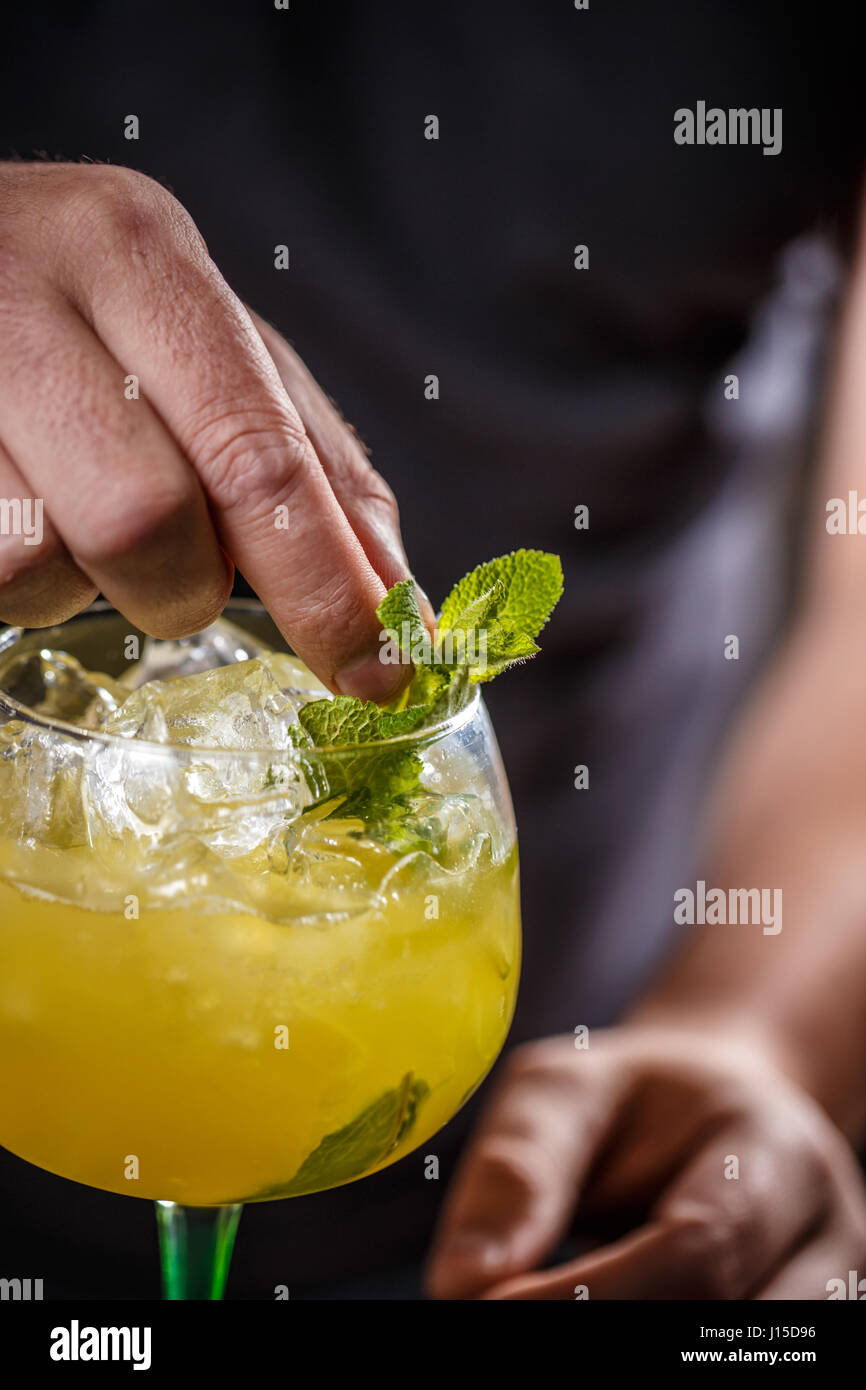 Barman is decorating cocktail with mint leaf - Stock Image