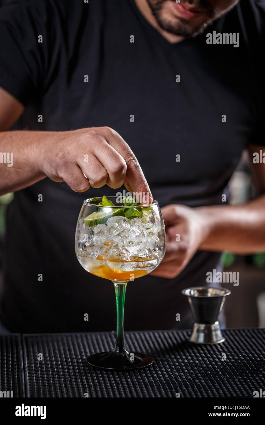 Barman is decorating a cocktail with a mint leaf - Stock Image