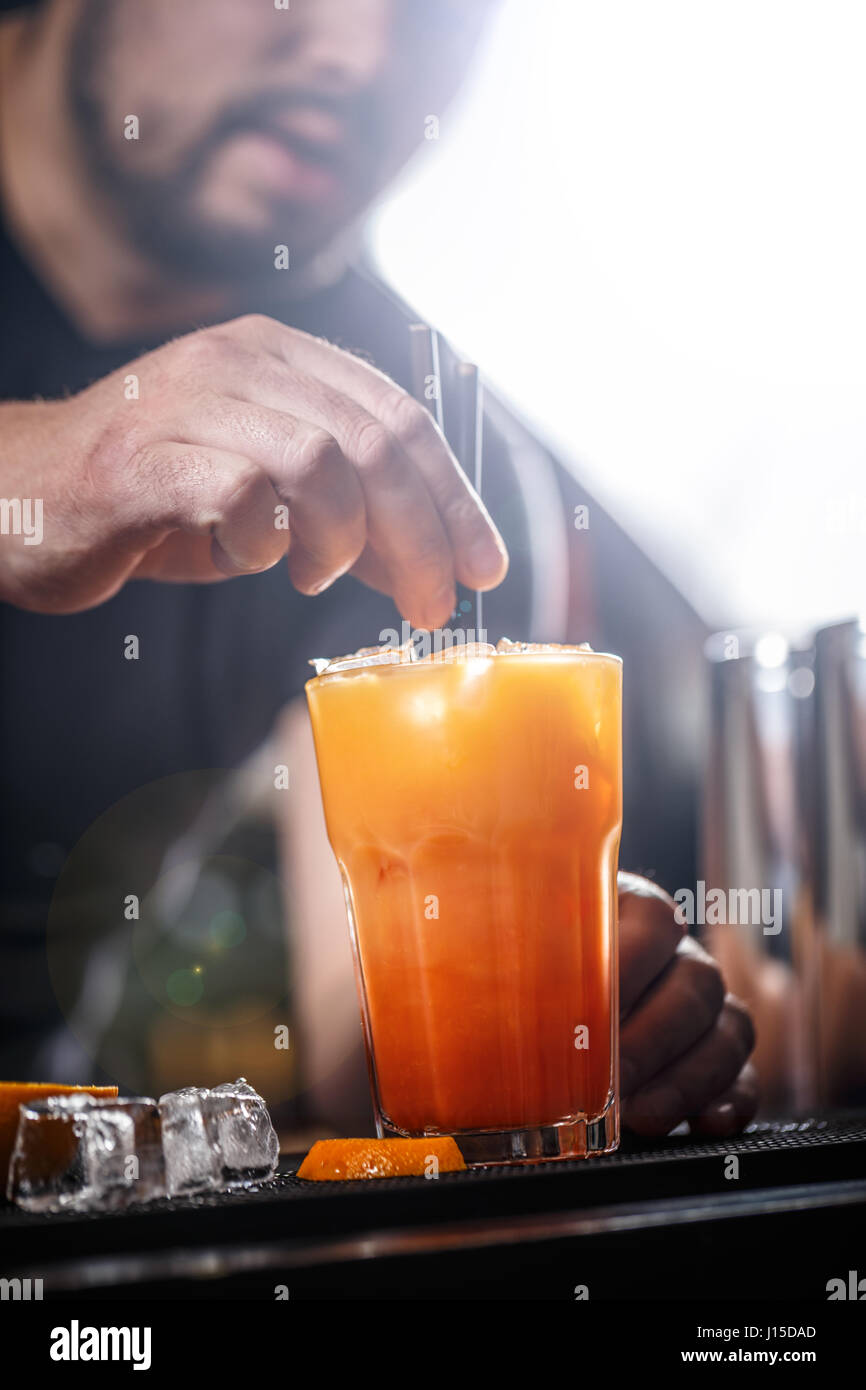 Barman at work, he is preparing cocktails, concept about service and beverages - Stock Image