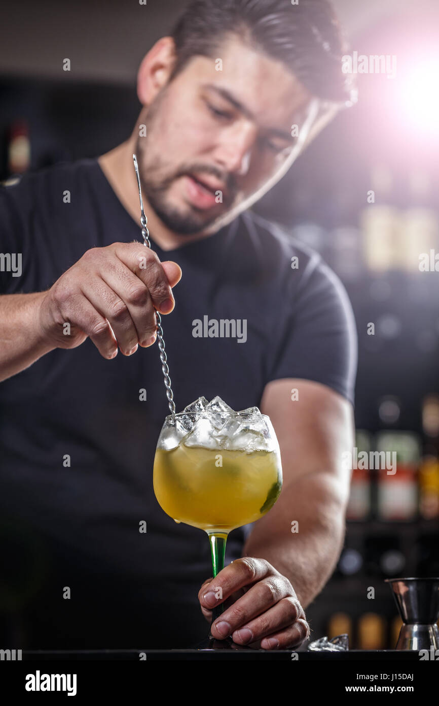 Bartender is stirring cocktails on bar counter - Stock Image