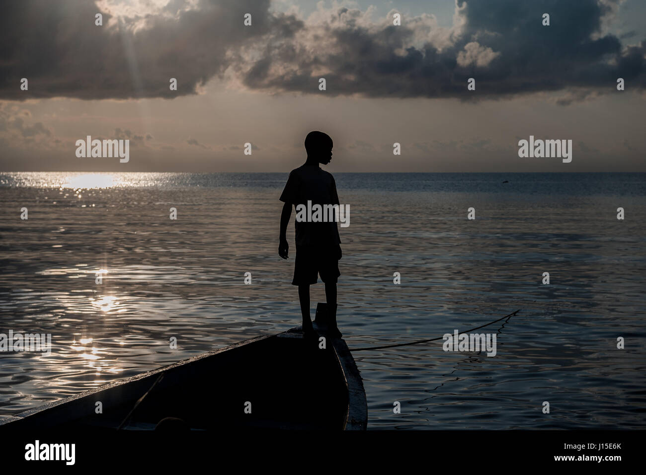 A young boy stands on the bow of a moored boat in Lake Malawi - Stock Image