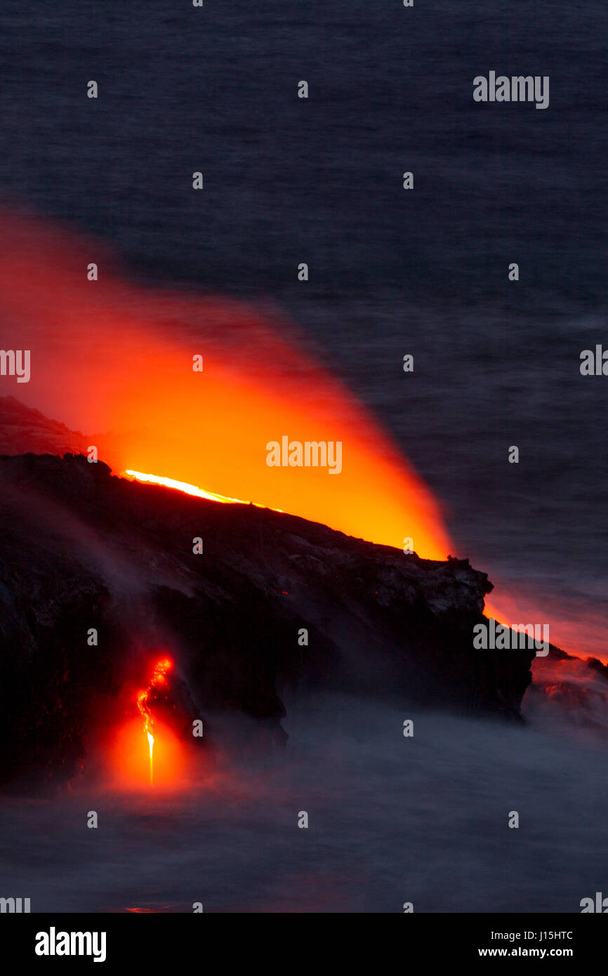 Red glowing lava flowing into the sea in the Hawaii Volcanoes National Park on Big Island, Hawaii, USA. - Stock Image