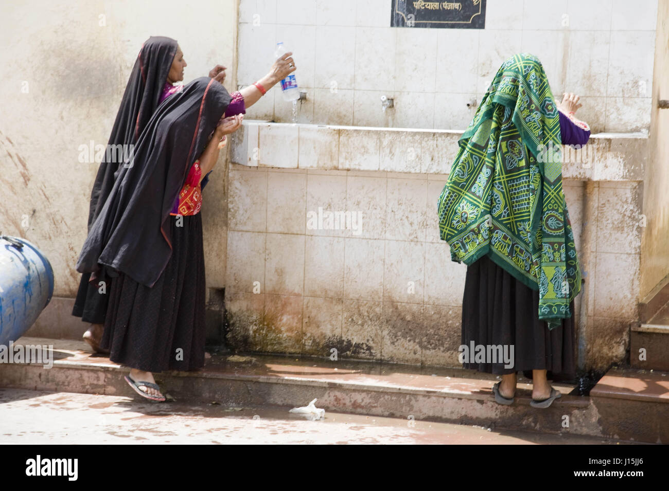 Women drinking cool water, vrindavan, mathura, uttar pradesh, india, asia - Stock Image
