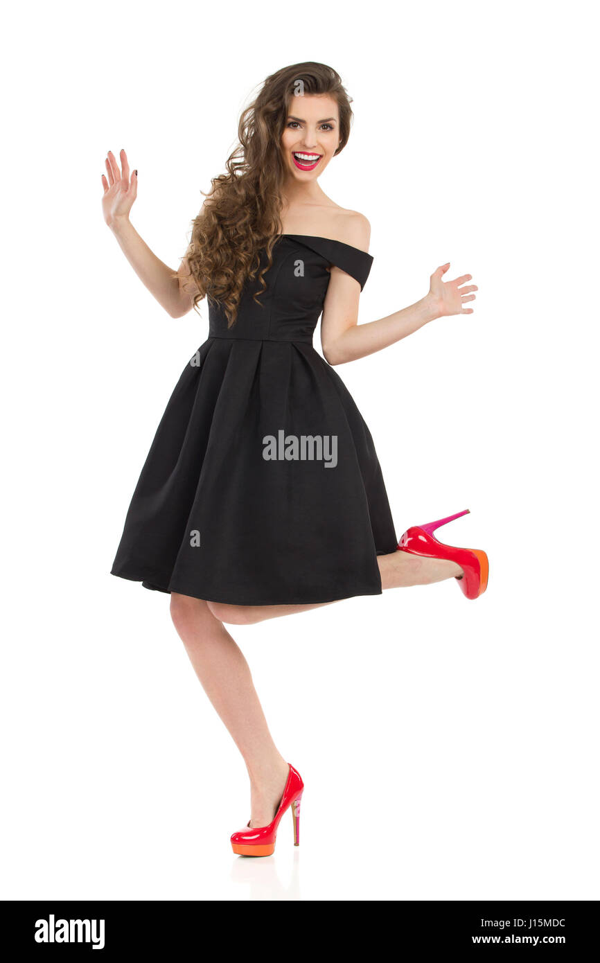 Beautiful young woman in elegant black cocktail dress and red high ...