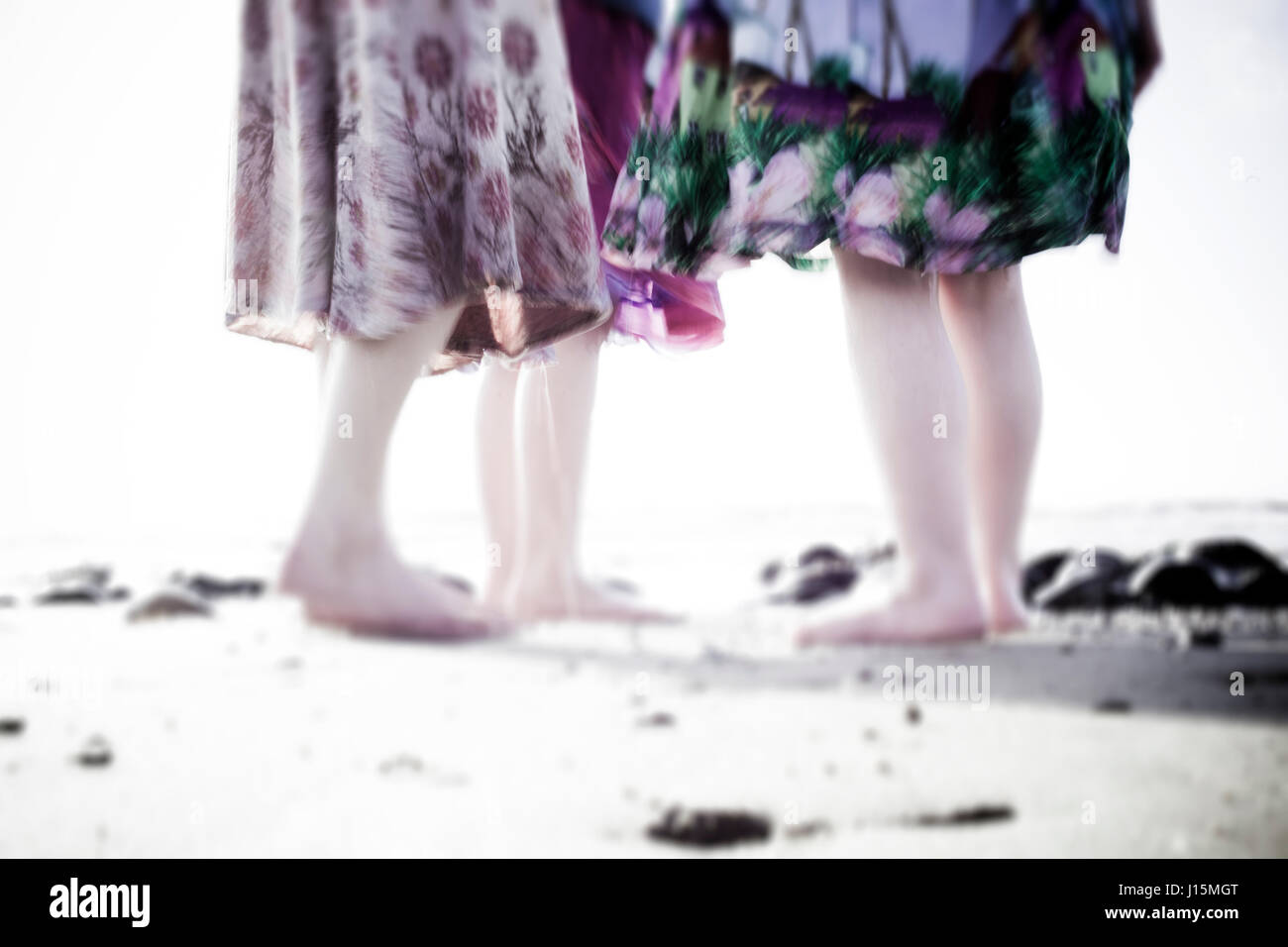 3 girls stand on a beach at sundown wearing cotton floral skirts and paddling on the edge of the shore. Movement - Stock Image
