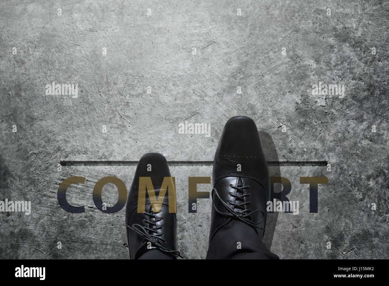 Comfort zone concept, Luxury Businessman step out of his safety boundary, Present by Black Leather shoes over a word and concrete floor, focus on righ Stock Photo