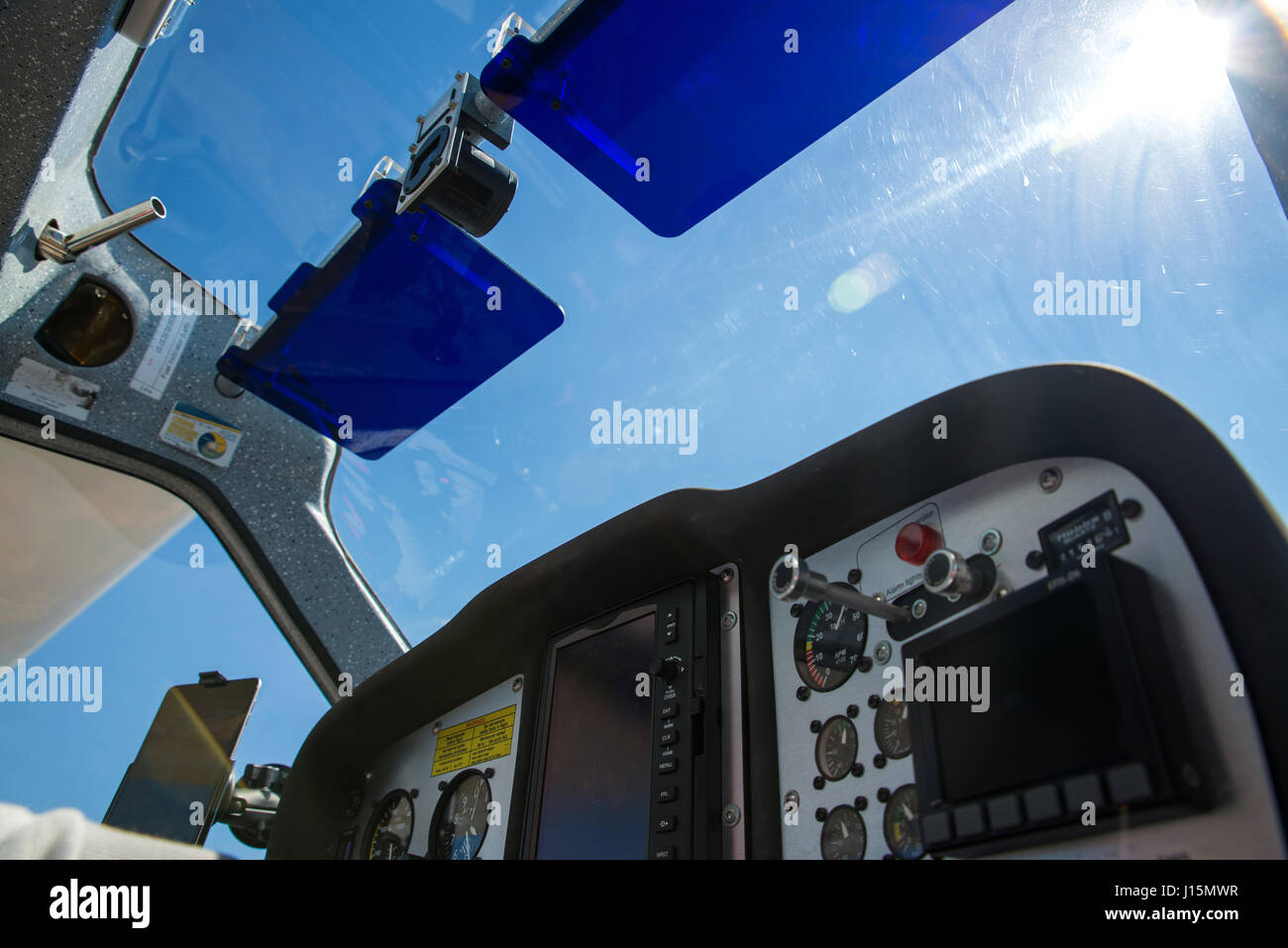 Low angle shot of a small aircraft cockpit flying at seven thousand feet. Selective focus on the sun visors and - Stock Image