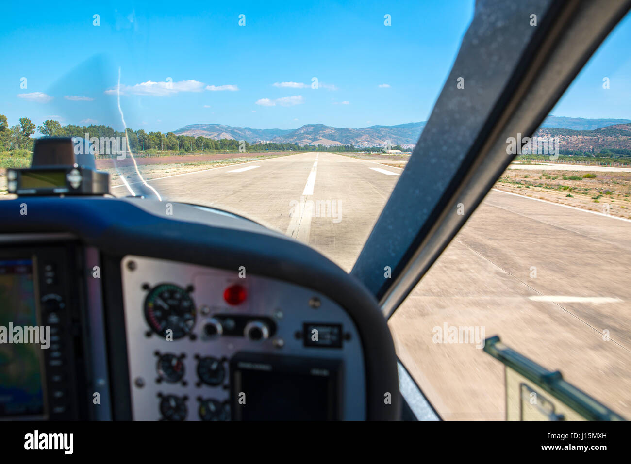 Small aircraft landing at a local airport. Blurry and out of focus cockpit, selective focus on the runway and the - Stock Image