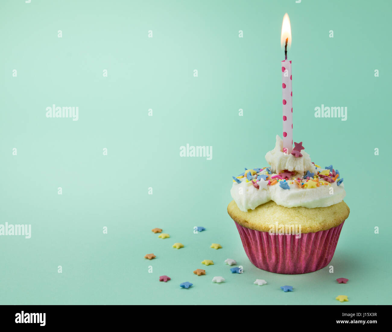 One cupcake with lit candle and star sprinkles isolated on green background - Stock Image