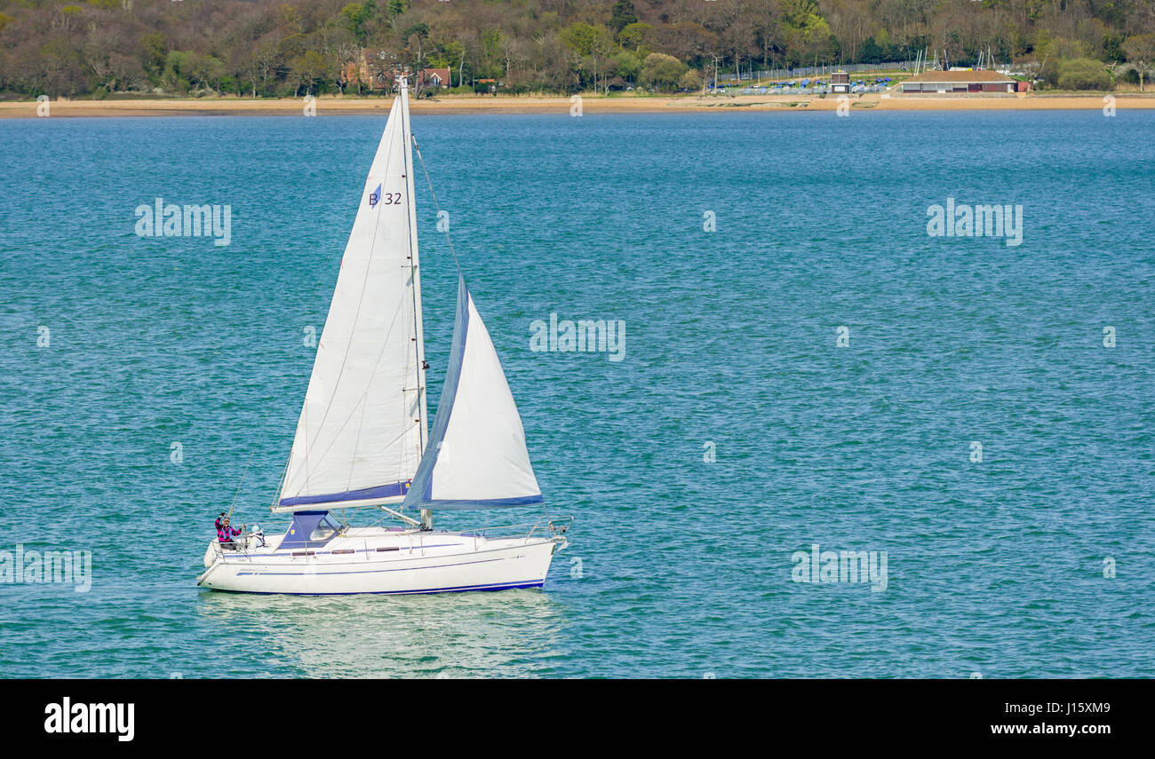 Small white yacht. Small yacht with sails up sailing on a narrow stretch of water near the Solent sea, with land - Stock Image
