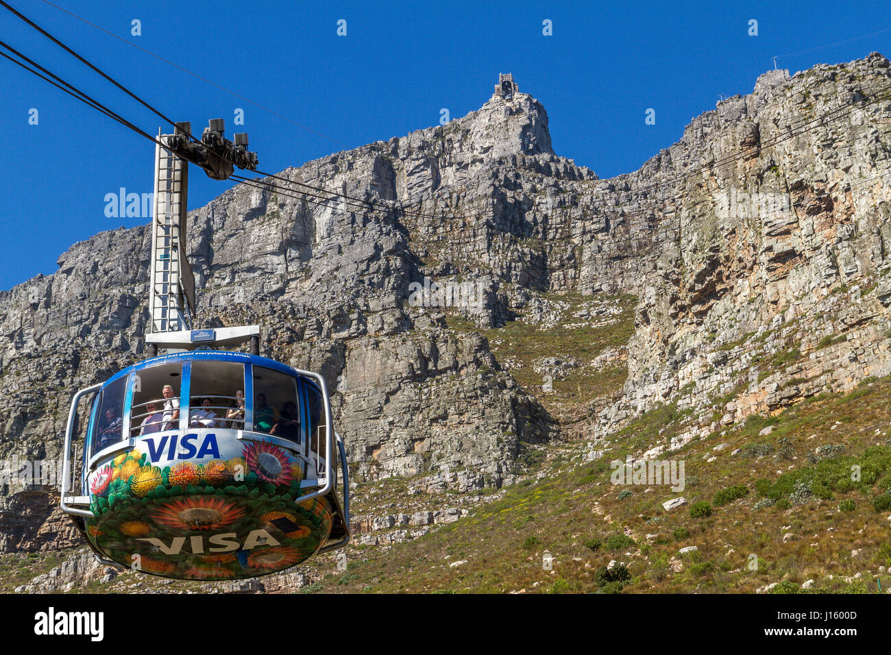Table Mountain Aerial Cableway cable car descends from the top of Table Mountain, a prominent landmark overlooking - Stock Image