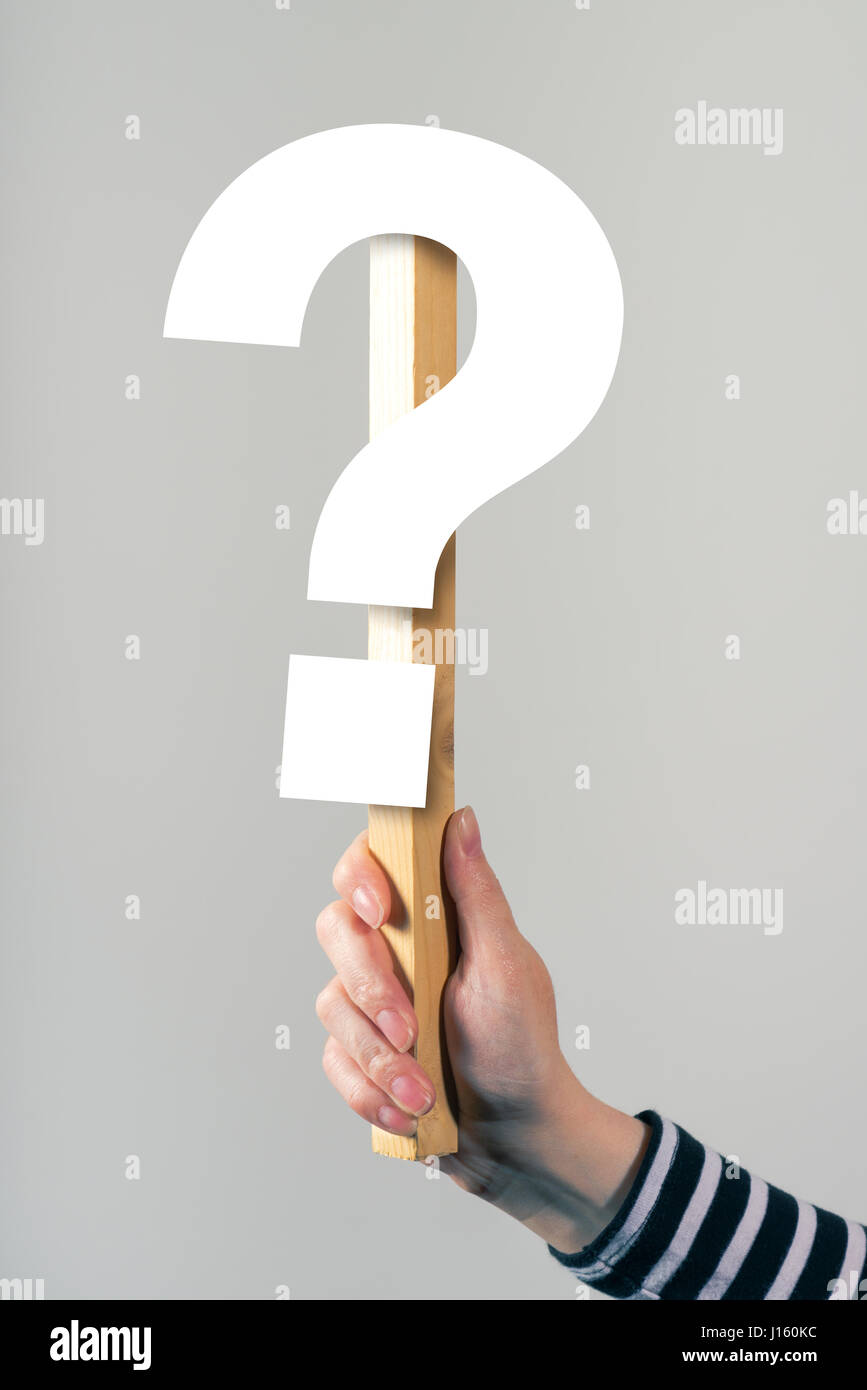 Woman holding question mark sign in hand - Stock Image
