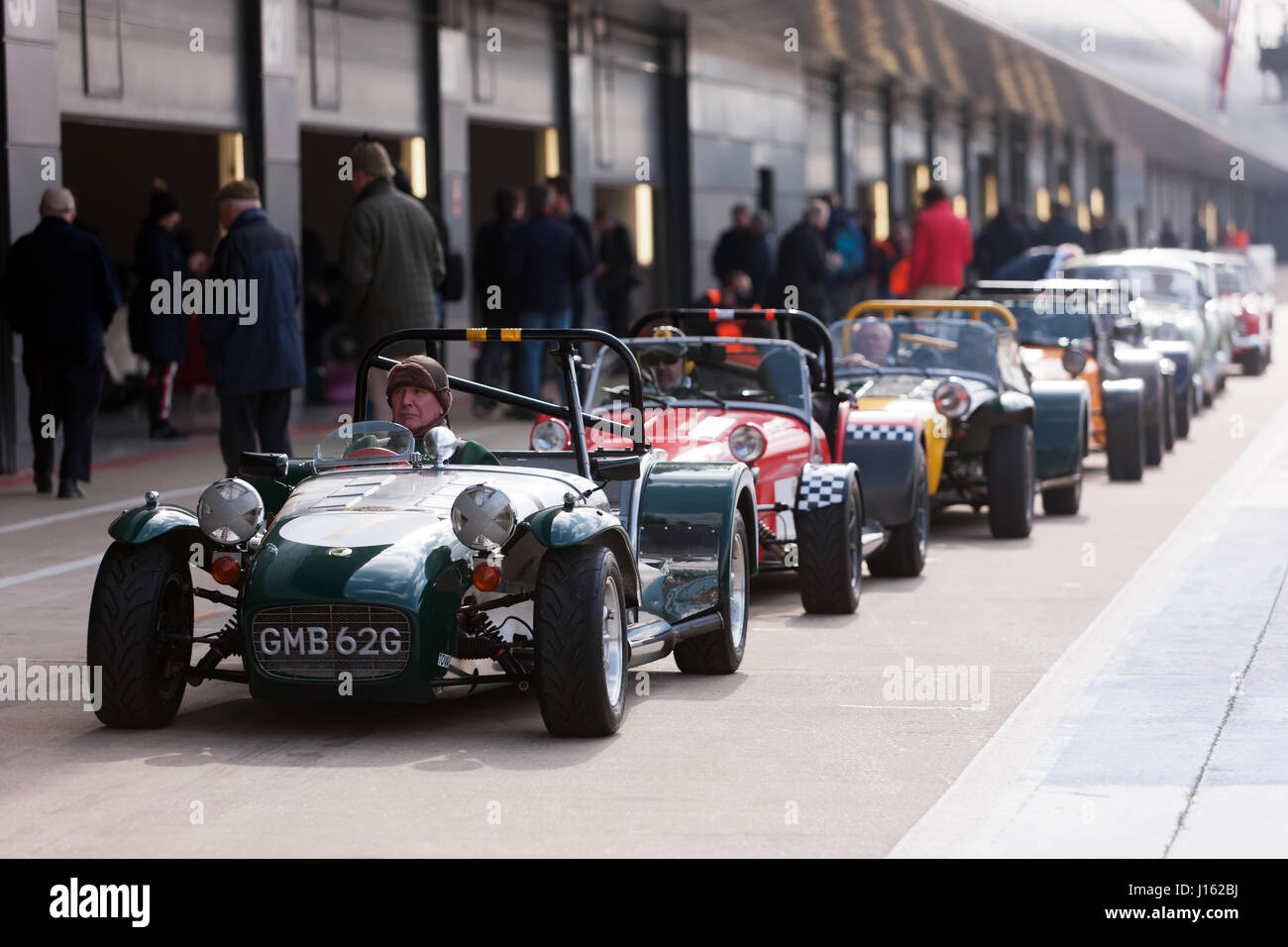 A group of classic Lotus 7 sports cars prepare to parade around the track, during the Silverstone Classic Media - Stock Image