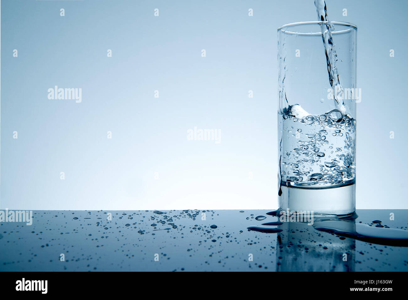 water splashing from glass with copyspace and blue toned - Stock Image