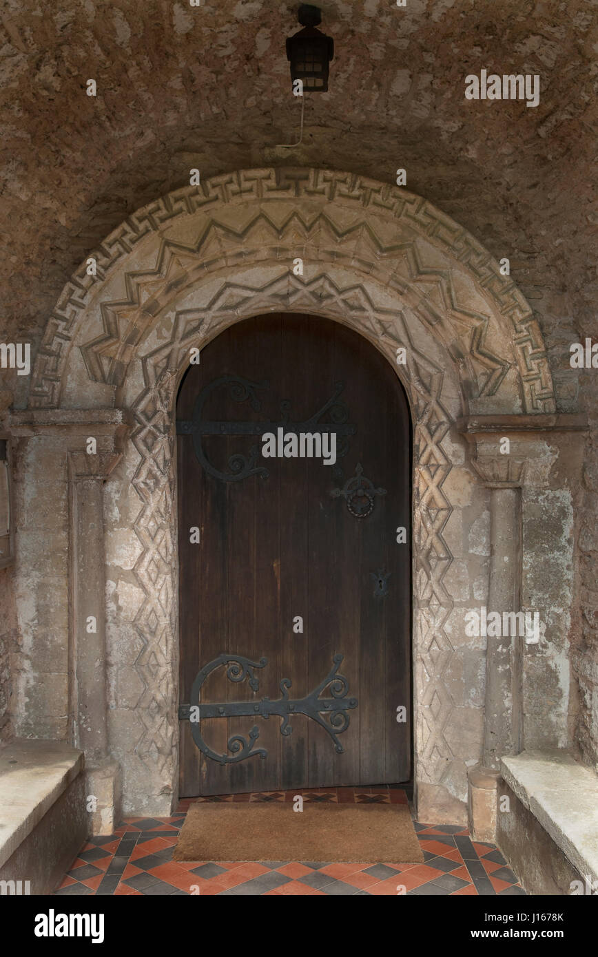 Norman arched doorway with ornamental zigzags forming lozenges on two faces of the round headed arch. Church of - Stock Image