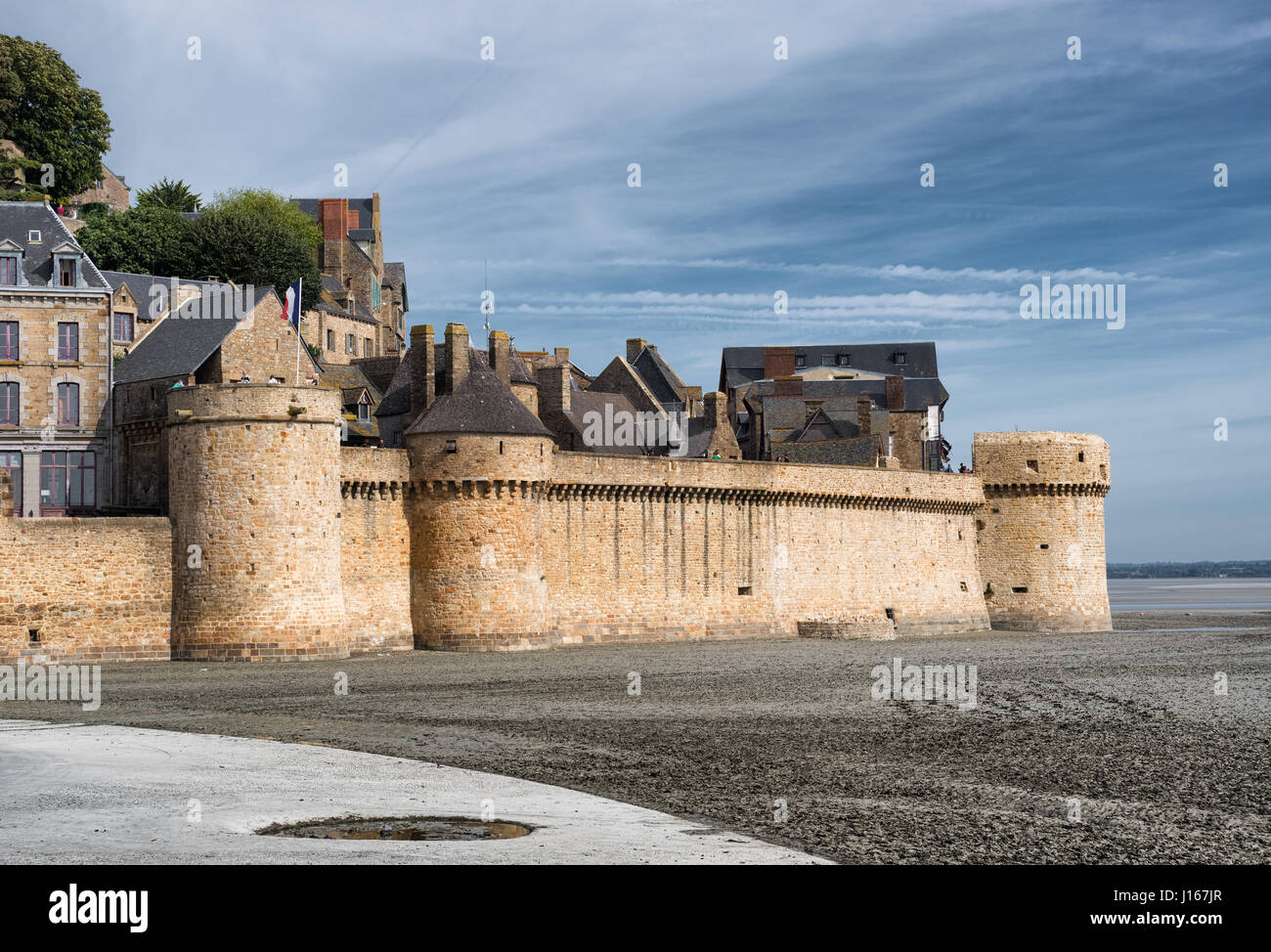 Panoramic view on the stone wall fortifications of Mont-Saint-Michel abbey, France - Stock Image