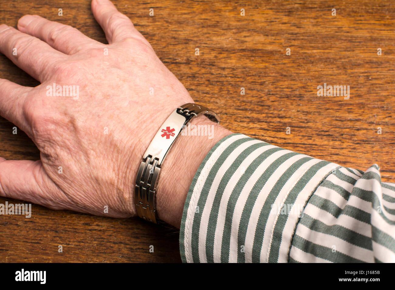 A medical alert wristband on a man's wrist - Stock Image