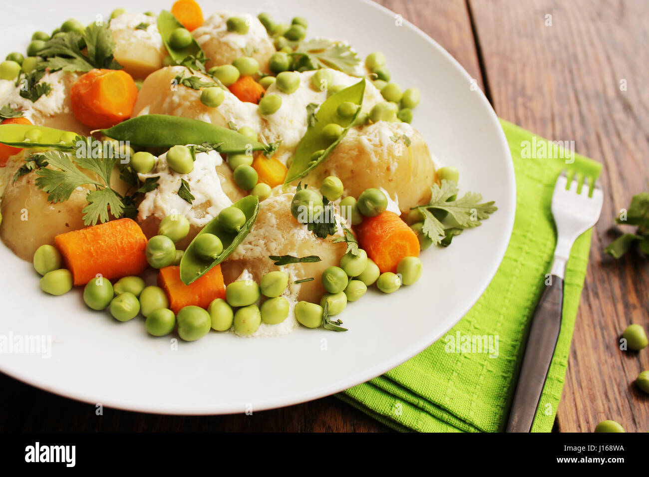 Potato salad with carrots, peas and coriander - Stock Image