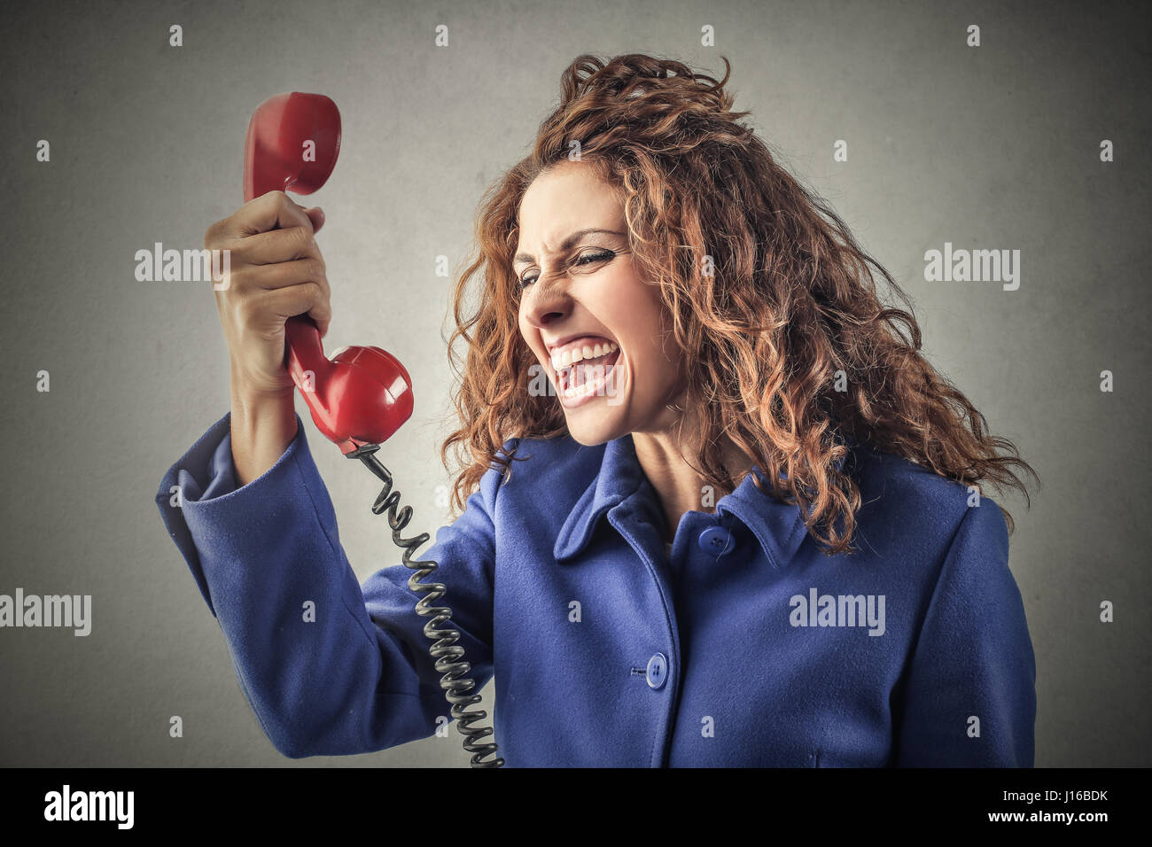 Curly woman yelling with phone - Stock Image