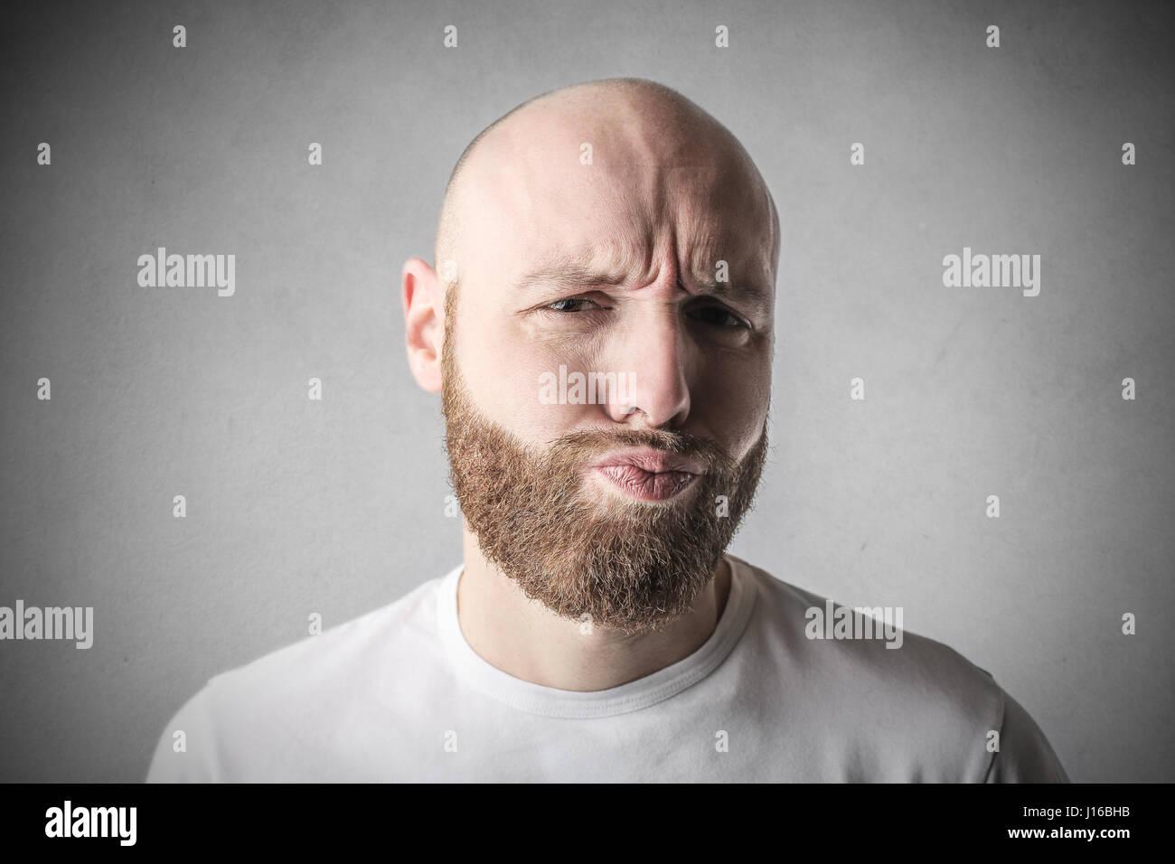 Bearded man making grimace - Stock Image