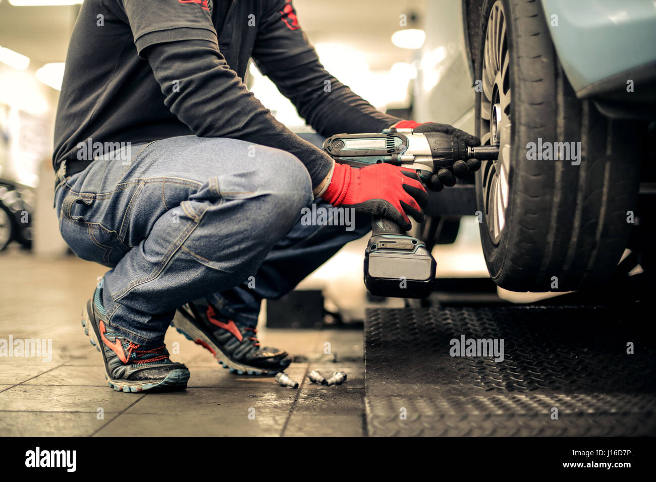 Mechanic man working with a tire - Stock Image