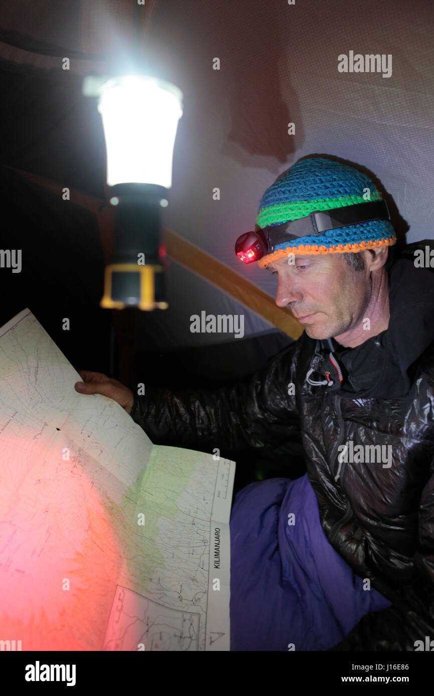 A Man Sitting In A Sleeping Bag Inside A Tent Looking At The Map Of Mount Kilimanjaro - Stock Image