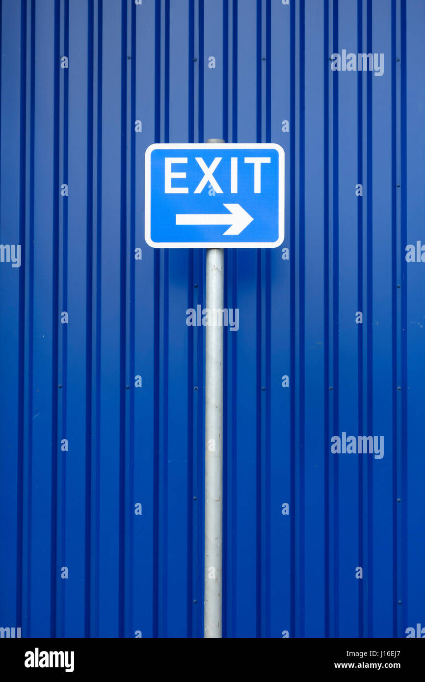 A blue 'exit' sign points to the right, against a blue background. Conceptual image of hardline Tory politics - Stock Image