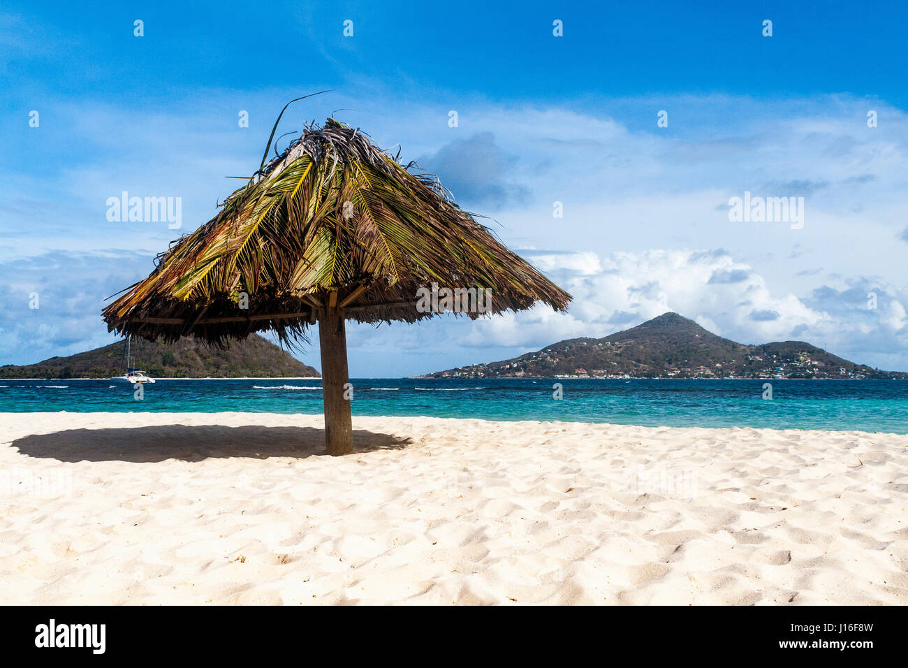 Caribbean View from Mopian Island: Solitary Parasol and Islands: Saint Vincent and the Grenadines. - Stock Image