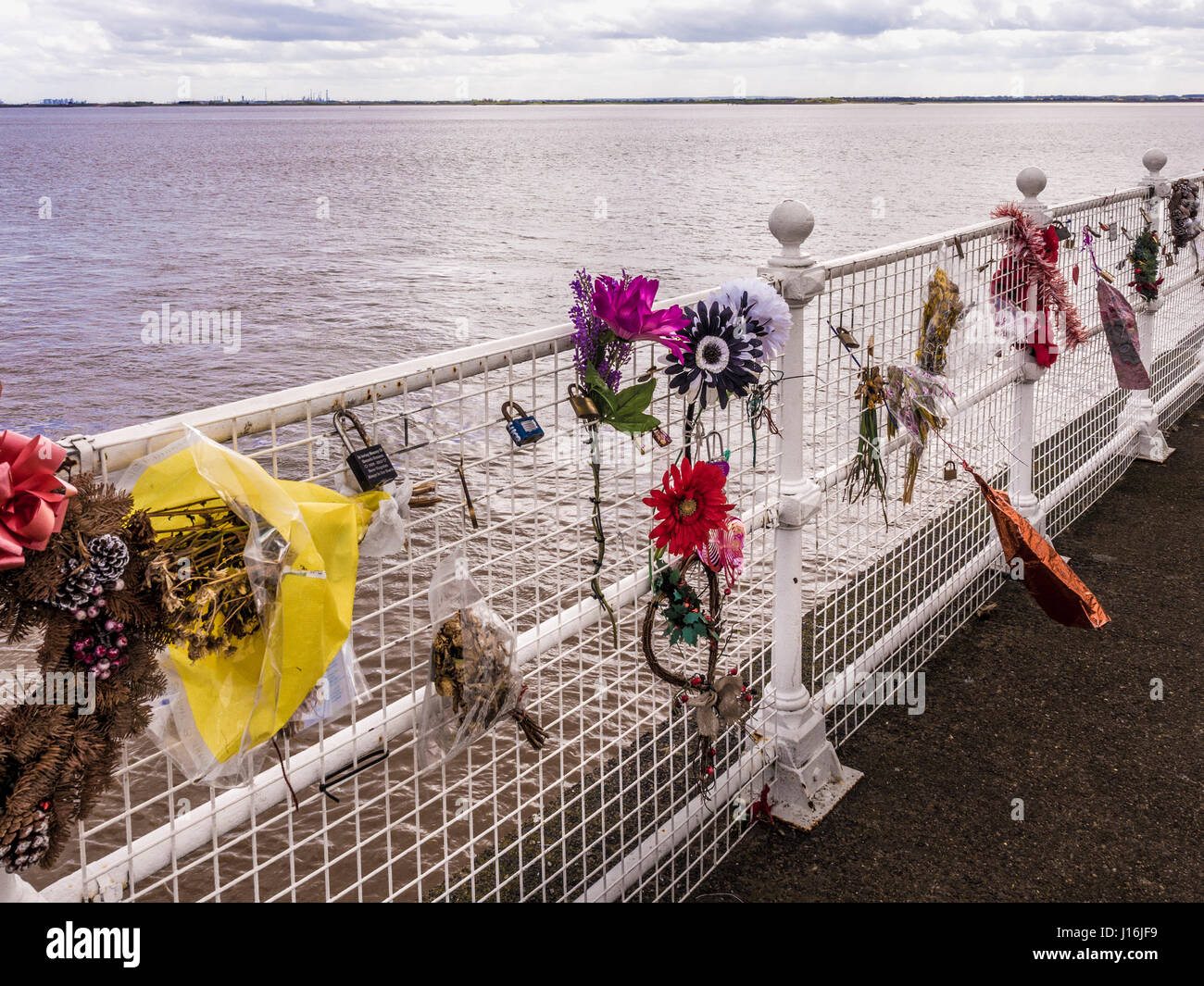 Flowers tied to railings with the Humber Estuary in the background to commemorate dead friends and relatives lost - Stock Image