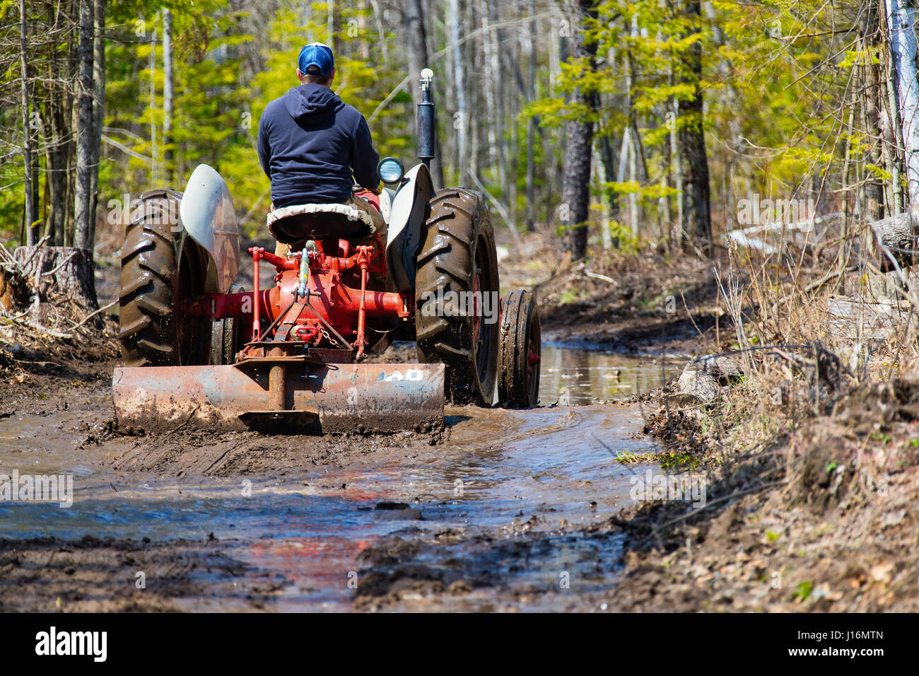 Man driving an old tractor while grading a muddy road. - Stock Image